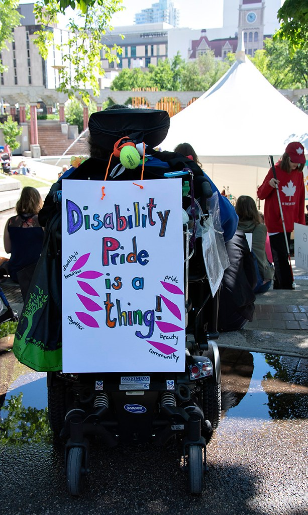 Wheelchair with sign saying Disability pride is a thing!