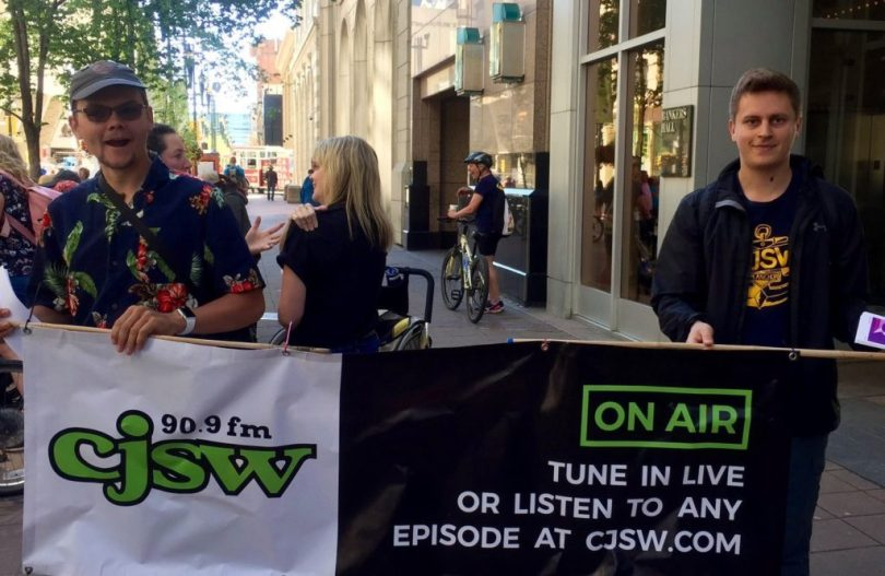 Two men holding banner for CJSW radio station