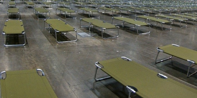 rows of cots in an emergency shelter