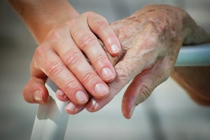 younger person's hand on top of older person's hand