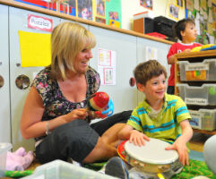 Teacher and student playing instruments on floor in classroom.
