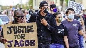 "Protesters marching, one holds a sign that says ""Justice for Jacob"""