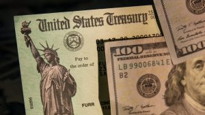 US Treasury check with cash bills on top