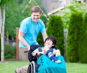 Man pushing child in a wheelchair - both smiling