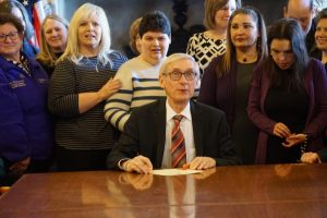 Governor Evers signs legislature with families standing behind him.