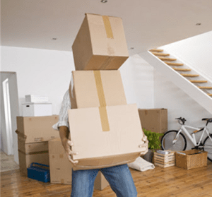 Man moving multiple large boxes through a room.