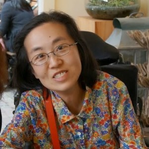 Image of an Asian American woman wearing glasses sitting in a wheelchair wearing a blouse with a flower print.