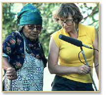 Image of a white woman holding a microphone outdoors listening to an older African American talk. They are both looking at something on the ground.