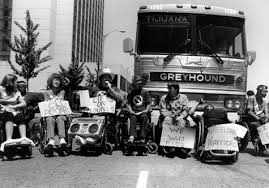 Black and white photo of ADAPT members, people with disabilities, protest in front of an inaccessible Greyhound bus.