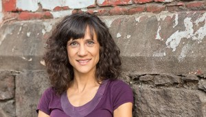 Head shot of Cheryl Green: a middle aged white woman with long brown curly hair wearing a purple t-shirt