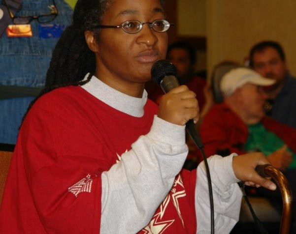 An African-American woman in a long-sleeved red and white shirt. She is wearing eyeglasses and holding a microphone at a meeting.