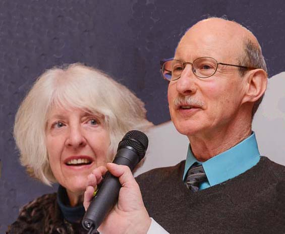 Image of a couple giving a talk. An older white woman with shoulder-length white hair is next to an older man with glasses and a mustache.