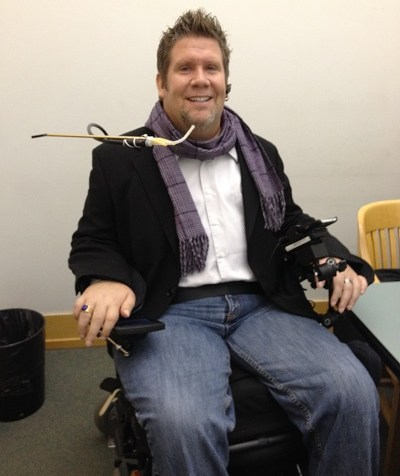 A man with spiky hair wearing a black jacket, white shirt and a scarf. He is sitting in a wheelchair with a sip-and-puff ventilator.