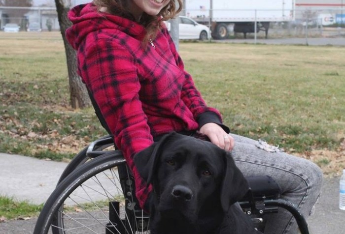 A young white woman in a manual wheelchair. She has a black labrador sitting in front of her.