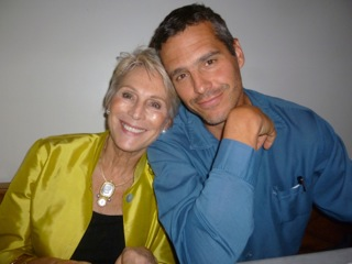 On older white woman leaning against her adult son. She is wearing a yellow silk jacket and he is wearing a blue shirt.