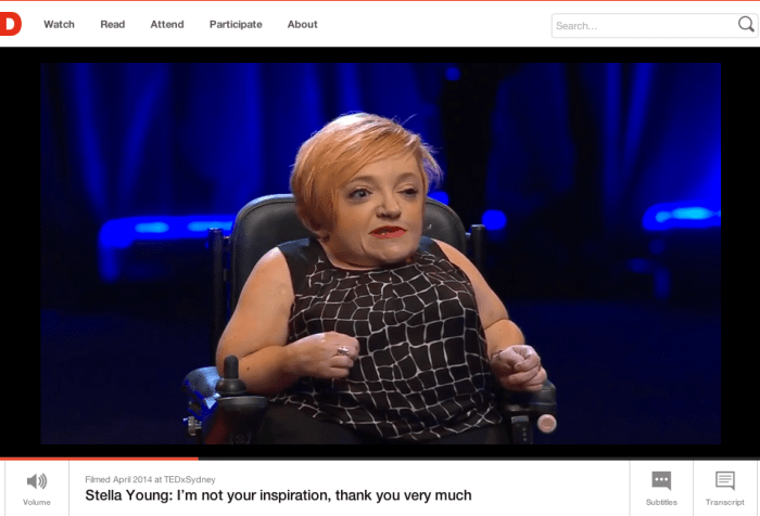 Screenshot from Stella Young's TED talk. Image of a small white woman with short red hair sitting in a wheelchair on a stage. The background is dark with blue lighting.
