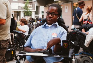 African American man in a wheelchair wearing glasses looking very seriously at the camera.