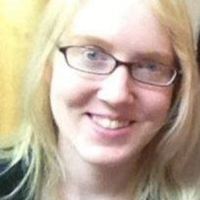 Picture of a young white woman with long blonde hair. She is smiling at the camera and wearing glasses.