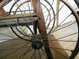 Profile view of a wooden wheelchair with large wheels and spies. The seat is made of wood.