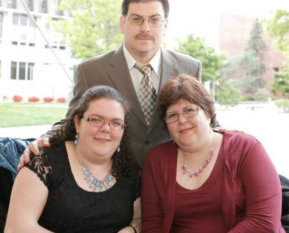 Photo of three family members in a photo. In the front is a white young woman sitting in a wheelchair on the left. On the right, is a middle aged white woman in a wheelchair on the right. Behind the two women in a middle aged white man. All three have brown hair and are wearing glasses.