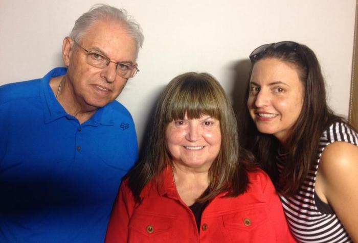 Photo of three individuals: On the left is an older white man wearing glasses and a blue t-shirt. In the middle is an older white woman with long brown hair and a red shirt. On the right side is a younger woman with long brown hair. All three are smiling at the camera.
