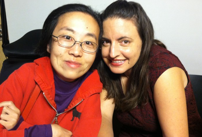 Photo of an Asian woman in a wheelchair w/ glasses wearing a red hoodie. She is on the left-hand side and on the right is a white woman with long brown hair and a magenta short-sleeve top. Both are smiling.