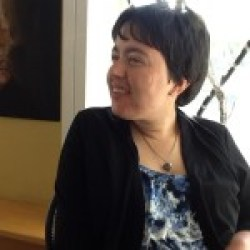Picture of a white woman seated in a chair. Her head is turned to the right and she's smiling. She has short dark hair and is wearing a floral-print top with a black jacket.