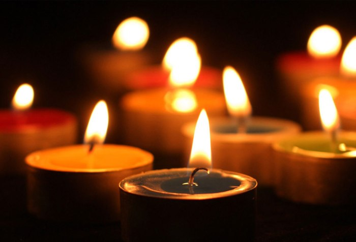 Image with a dark background, suggesting night time with several votive candles lit in a vigil or ceremony of some kind.