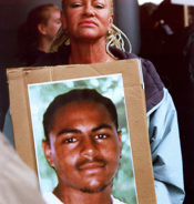 Older black woman with long braids holding a large poster with a photo of her son, a young African American man