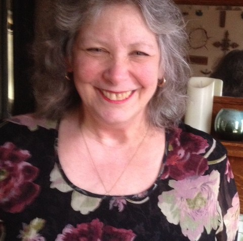 An older white woman with long gray hair. She is wearing a black top with flowers.