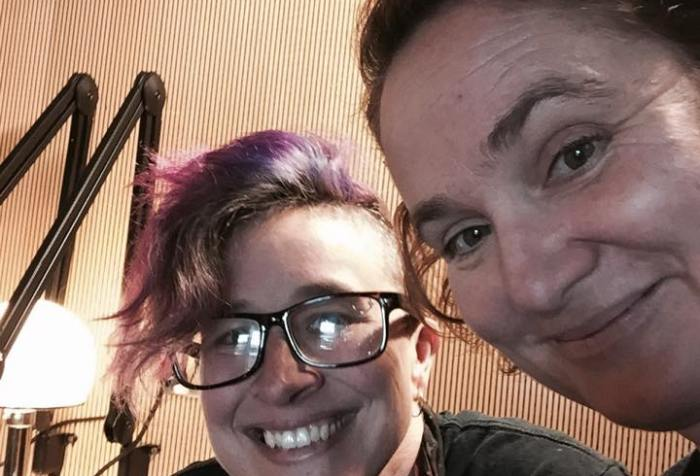 Image of two white women in a recording studio. The one in the center has a mohawk w/ pink highlights. She is wearing glasses. The woman on the right side has short red hair and she is smiling.