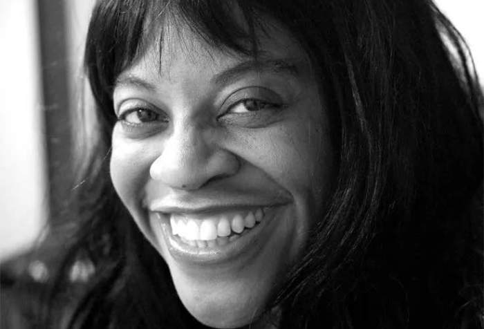 Black and white image of a middle aged African American woman with long hair smiling at the camera.