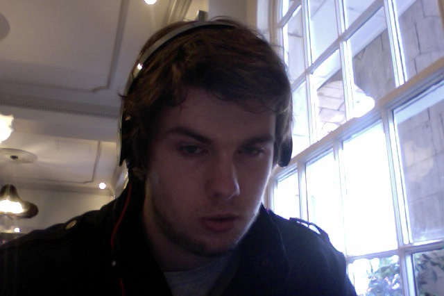 Image of a white man with brown hair staring at the camera. He is wearing headphones.