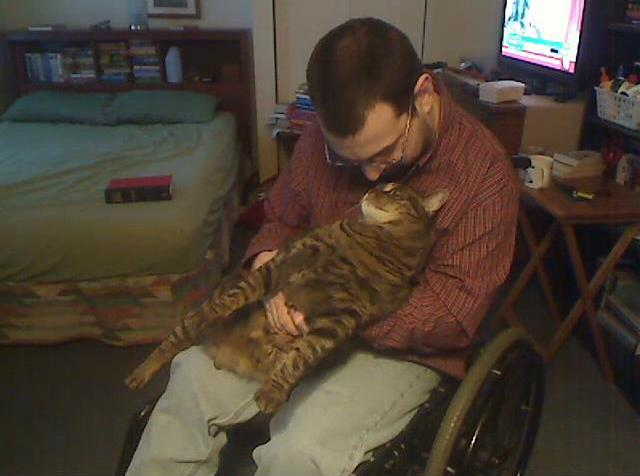 Image of a white man in a wheelchair. His head is bent down toward the face of his cat, a Maine coon, who is sitting on his lap.