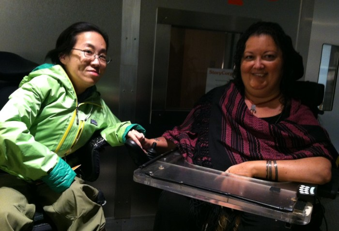 two women of color in wheelchairs in front of a recording booth. The woman on the left is wearing a green jacket, glasses, and has black hair. The woman on the right has long curly dark hair, a black and magenta top and a tray attached to her wheelchair. Both are smiling.