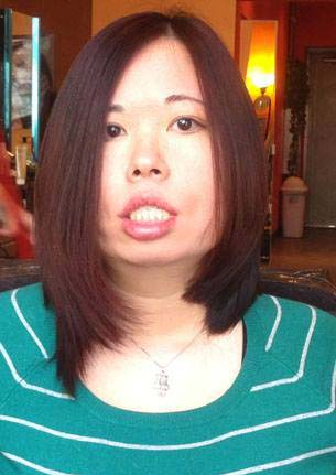 Middle-aged Chinese American woman with long hair. She is wearing a green sweater and white-stripes. A living room background is behind her.