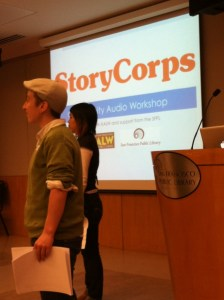 "Two people standing profile facing the left side of a room, in the backdrop is a projector screen with the words, ""StoryCorps"" in large orange letters"