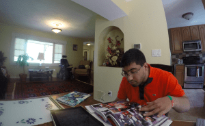 Young Pakistani American man with dark hair and glasses sitting at a table reading a comic book.