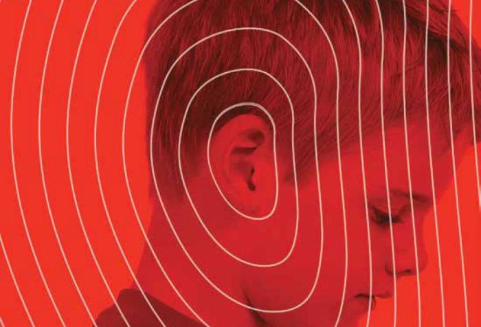 Image description: A book cover featuring a profile photograph of a young, white boy as he looks slightly downward. The picture is a saturated red color with white lines emanating from the boy's ear outward to the edge of the book, suggesting sound waves. Overlaid on that in white letters is the title of the book, Made to Hear: Cochlear Implants and Raising Deaf Children. Below the title appears the name Laura Mauldin.