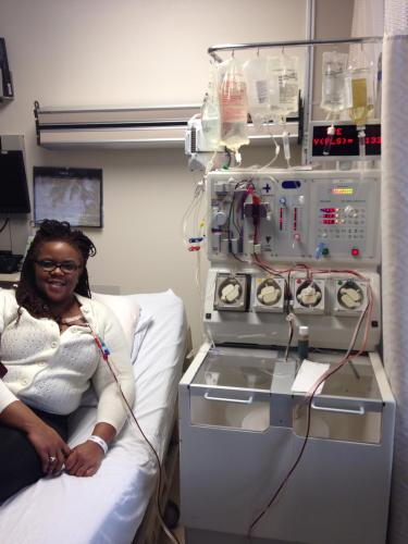 A Black woman on a hospital bed and she is receiving a blood transfusion. There is a tube with blood connected to a large machine with hanging bags of blood.