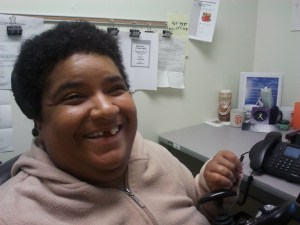 An African American woman with short black hair. She's inside an office and sitting nearby a table with a computer. She's wearing a beige pullover and smiling at the camera.