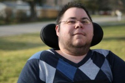 Photo of Dominick Evans, a transgender man with short dark hair and glasses. He has stubble around his chin and neck. He is in a wheelchair with a black headrest behind him. He is wearing an argyle-print sweater in different shades of blue.