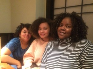 A Black woman with curly hair wearing a striped turtleneck. The the left of her are her two teenage biracial daughters, both with curly hair.