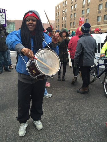 A Black woman with long braids wearing a blue jacket with a hoodie. She has a drum around her body and is holding two drumsticks.