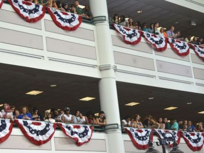 Two floors with crowds overlooking the a large indoor space. People have their smartphones out. Patriotic bunting is hung on both floors.