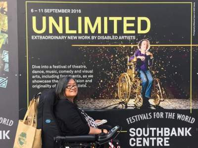 "Profile view of an Asian woman in black wheelchair. She has a brown shopping bag hanging on the back of her wheelchair. Behind her is a large billboard for ""Assisted Suicide: The Musical"" showing at the Southbank Centre in London. The word UNLIMITED is in gold. The billboard shows a thin petite white woman in a gold manual wheelchair sprinkled in gold confetti."