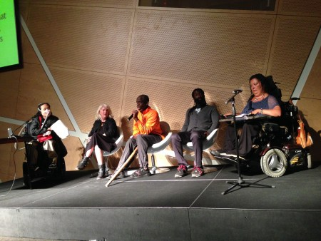 Image of a stage with five people sitting and having a conversation. There is an Asian American woman in a wheelchair on the very left with a small table in front of her. To her right is a white woman with white-blonde hair and a black dress. Next to her is an older Black disabled man with a bright orange shirt and a wooden walking stick. Next to him is a younger Black man with long dreadlocks and a beard. He is wearing a gray top and dark pants. The final person on the right side of the stage is a woman of color in a wheelchair with a blue top and a table connected to her wheelchair.