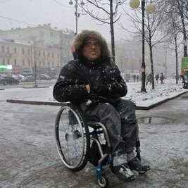 A middle-aged white man wearing eye glasses. He is sitting in a manual chair outdoors on a gray snowy day. He has on a winter jacket with a furry hood. His hands are stuffed in his pockets. The background is an urban setting with buildings, trees and sidewalks.