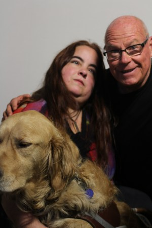 Photo of two people against a blank white background. An older white man with glasses has his arm around a young white woman with long brown hair. The man is wearing a black top and the woman is wearing a multi-colored top. In front of the woman is a golden retriever, her service animal.