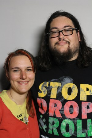 "Photo of two people against a blank white background. On the right is a tall young man with long dark brown hair, a beard and glasses. He is wearing a black t-shirt that says ""Stop, Drop, & Roll"" in yellow, red, and green for each word. Next to him on the left of the image is a young white woman with long brown hair and streaks of red highlights. She is wearing a red hoodie with a yellow t-shirt. Both are smiling at the camera."